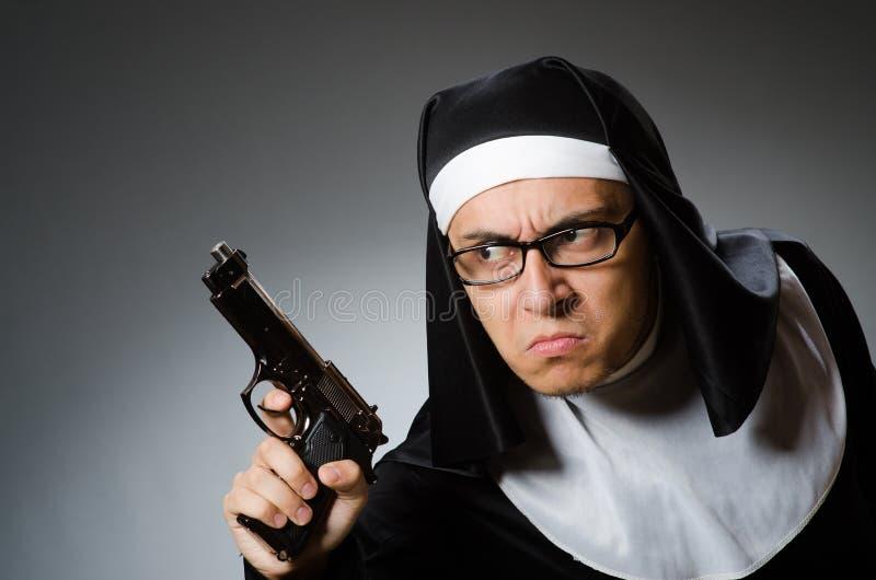 Человек одетый как монашка с личным огнестрельным оружием стоковая фотография