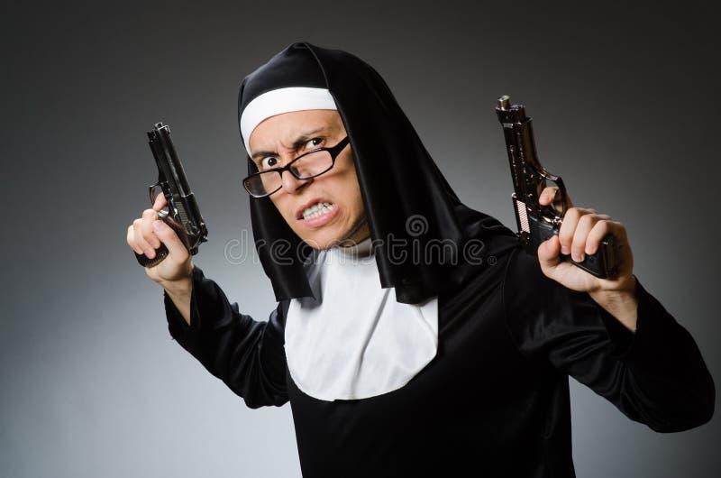 Человек одетый как монашка с личным огнестрельным оружием стоковое изображение