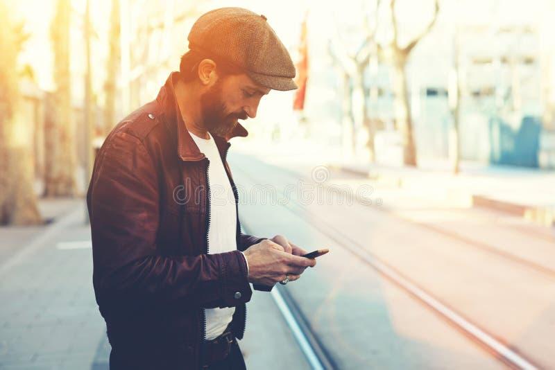 Человек одел в стильных одеждах беседуя на умном телефоне во время идти в холодный весенний день стоковое фото