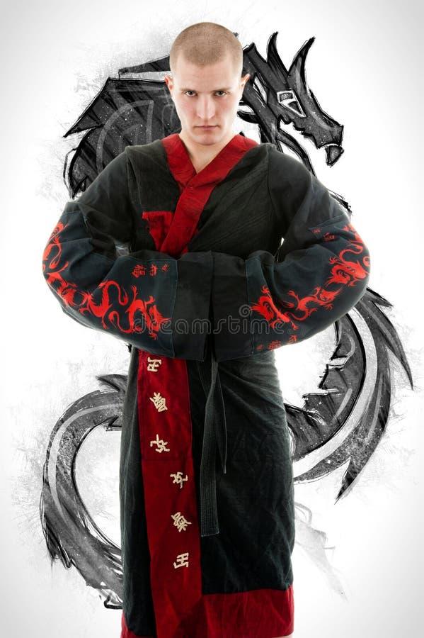 Человек одел в черном кимоно дракона демонстрируя боевые искусства co стоковое фото rf