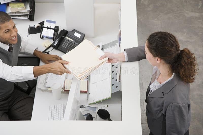 Человек передавая файл к коллеге стоковые изображения rf