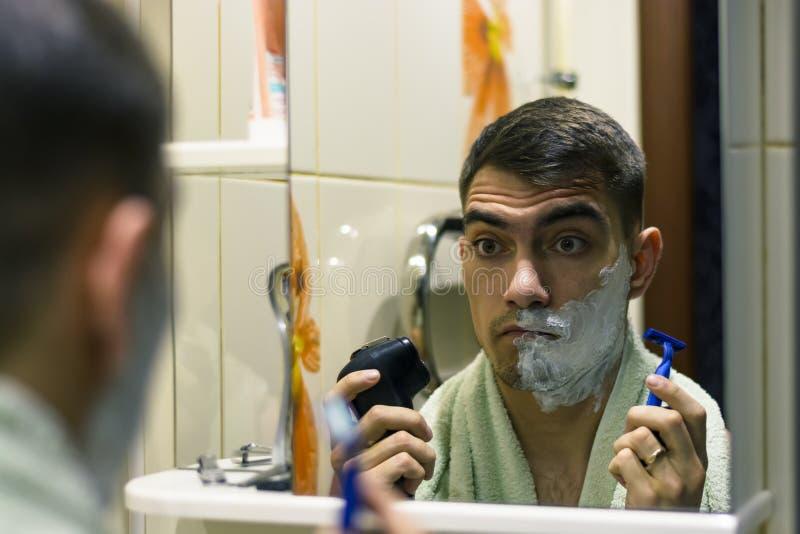 Человек перед отборным электрическим шевером или бритвами классическими стоковые фото