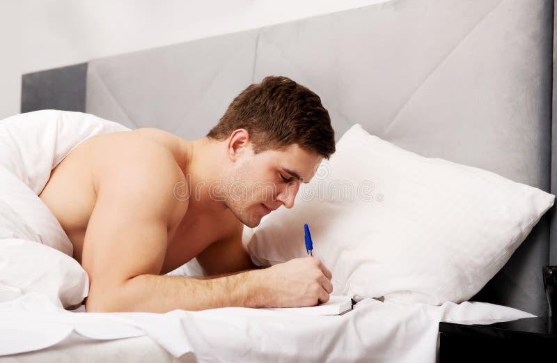 Человек писать примечание в его кровати стоковые изображения rf