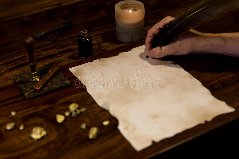 Человек пишет на старом пергаменте стоковое изображение