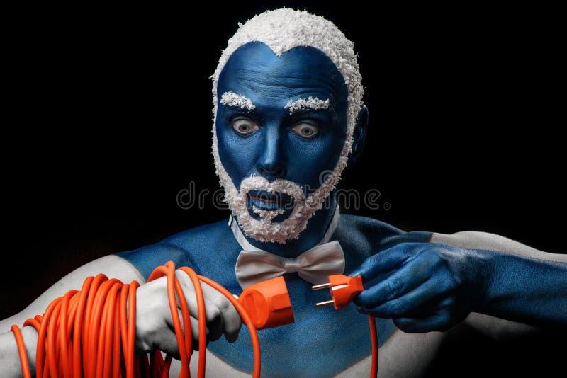 Человек покрашенный в голубом цвете с снежными волосами и бородой держит шнур питания с штепсельной вилкой стоковая фотография rf