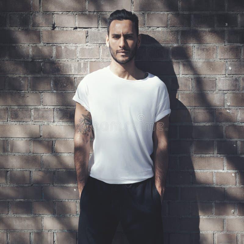 Человек портрета бородатый при татуировка нося пустую белую футболку и черные джинсы Предпосылка стены кирпичей Вертикальный моде стоковая фотография