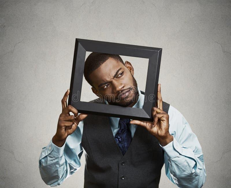 Человек портрета молодой смешной исполнительный вставляя голову в fram изображения стоковое фото rf