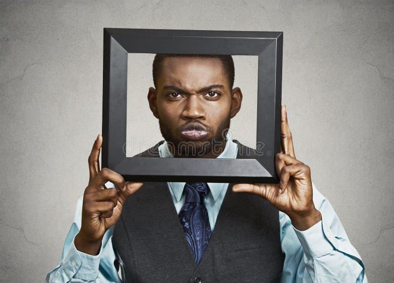 Человек портрета молодой смешной исполнительный вставляя голову в fram изображения стоковая фотография rf