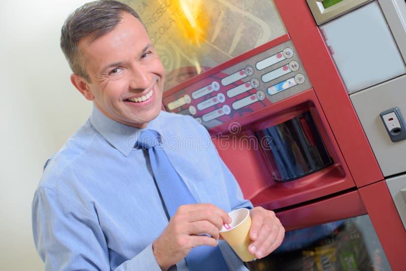 Человек получая кофе от торгового автомата стоковые изображения rf