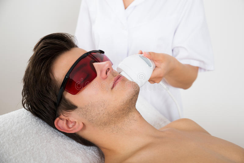 Человек получая обработку удаления волос лазера стоковая фотография rf