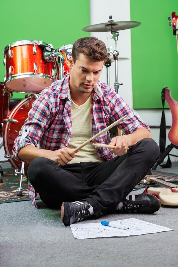 Человек практикуя с Drumsticks пока сидящ на поле стоковое изображение