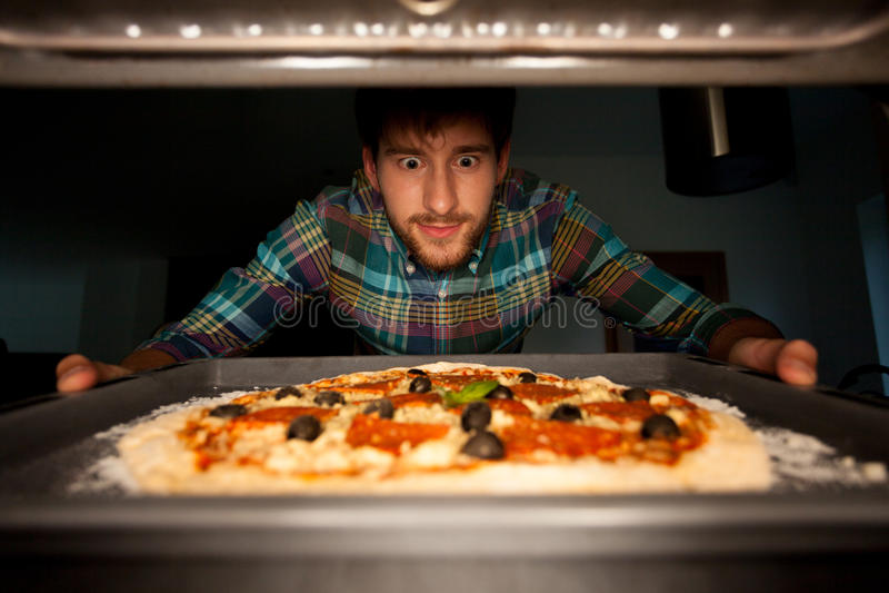 Человек принимая пиццу от печи стоковое фото rf