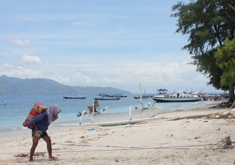 Человек приносит продовольственные ресурсы к острову стоковое фото