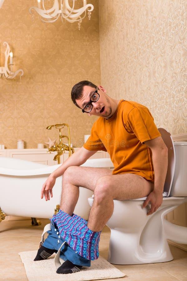 Человек при брюки вниз сидя на шаре туалета стоковая фотография