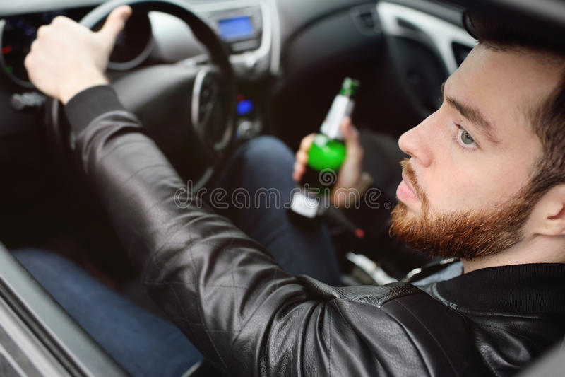 Человек при бутылка пива управляя автомобилем стоковое фото