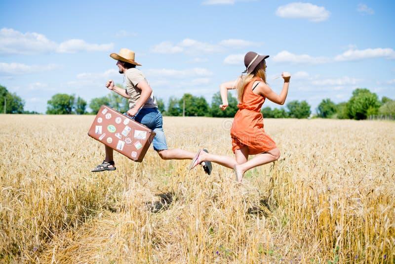 Человек при ретро чемодан и женщина бежать внутри стоковое изображение rf