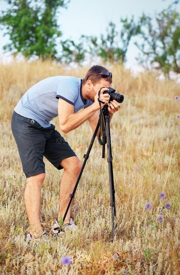 Человек при тренога и камера стоя на луге стоковое фото rf