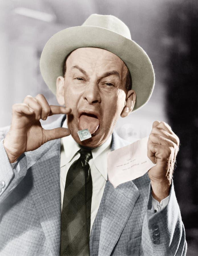 Человек при штемпель почтового сбора вставленный на его языке (все показанные люди более длинные живущие и никакое имущество не с стоковые изображения