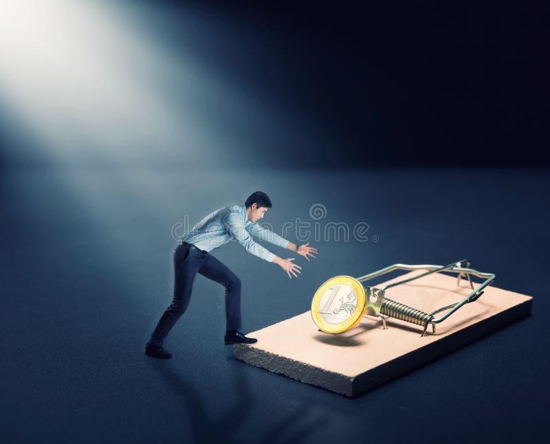 Человек пробуя выбрать золотую монетку стоковое изображение rf