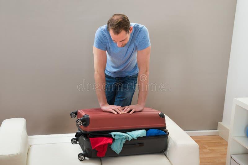 Человек пробуя закрыть чемодан стоковое изображение