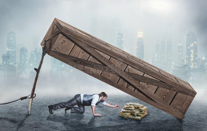 Человек пробуя получить деньги в ловушке стоковое фото