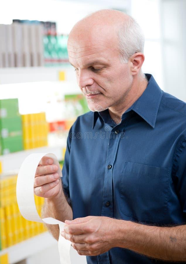 Человек проверяя получение бакалеи на магазине стоковое фото