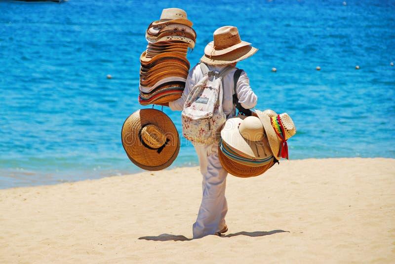Человек продавая шляпы на пляже стоковое фото