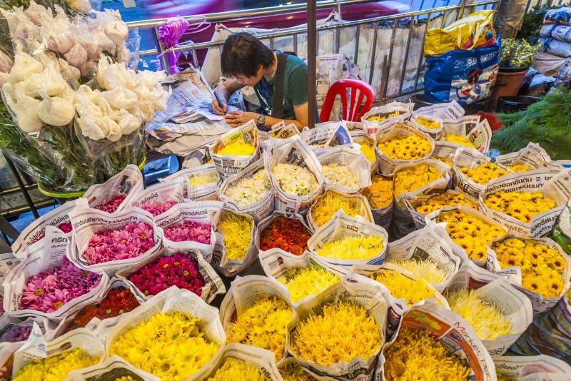 Человек продает красочные цветки на flowermarket в Бангкоке раньше стоковое фото rf