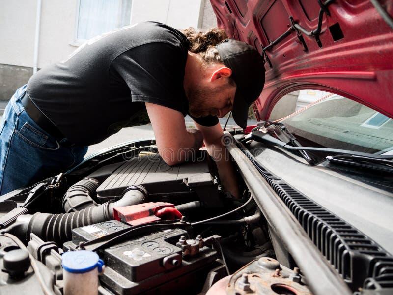 Человек работая на автомобиле стоковые изображения