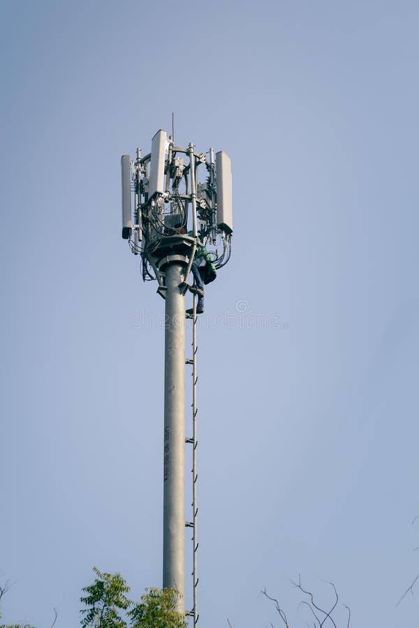 Человек работая на башне радиосвязи стоковое фото rf