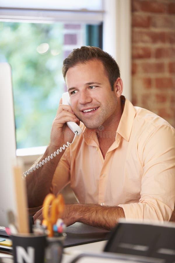 Человек работая на компьютере в современном офисе стоковое фото