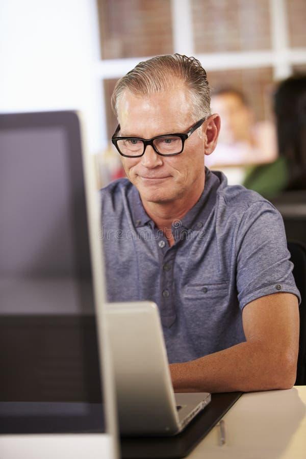 Человек работая на компьютере в современном офисе стоковое изображение