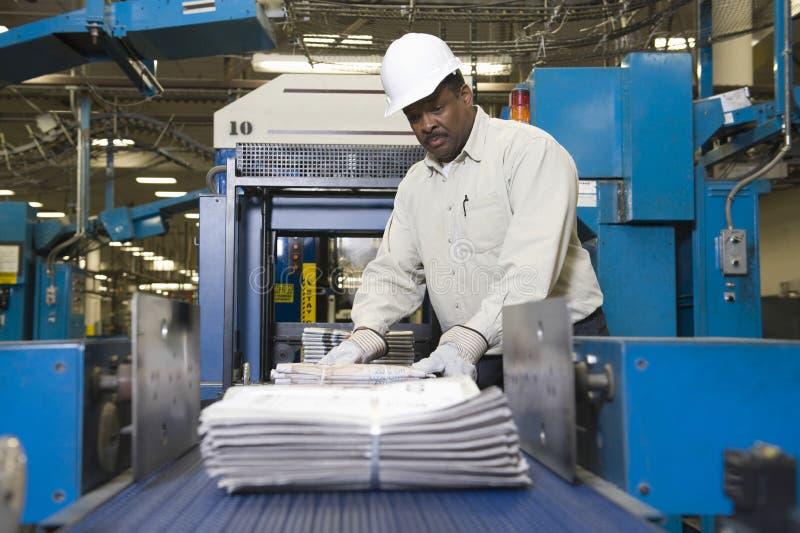 Человек работая на производственной линии газеты стоковая фотография rf