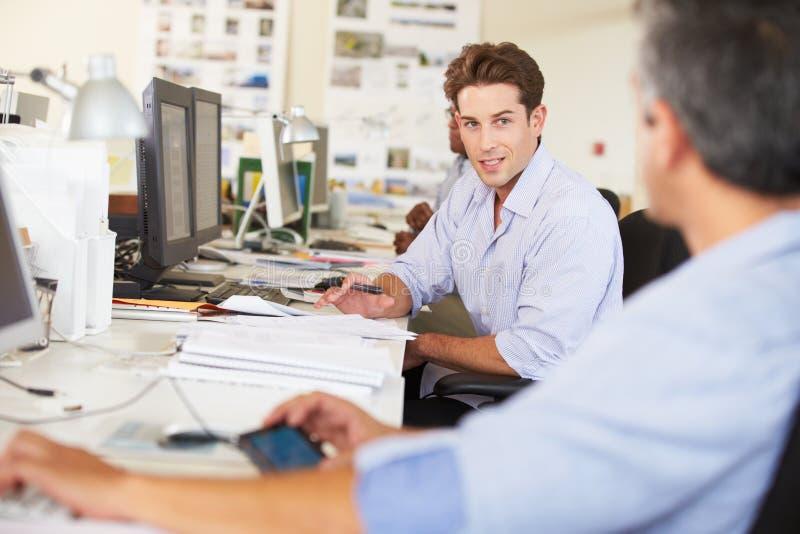 Человек работая на столе в многодельном творческом офисе стоковое фото