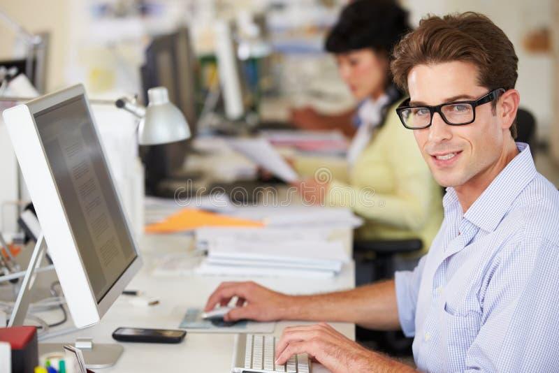 Человек работая на столе в многодельном творческом офисе стоковое изображение