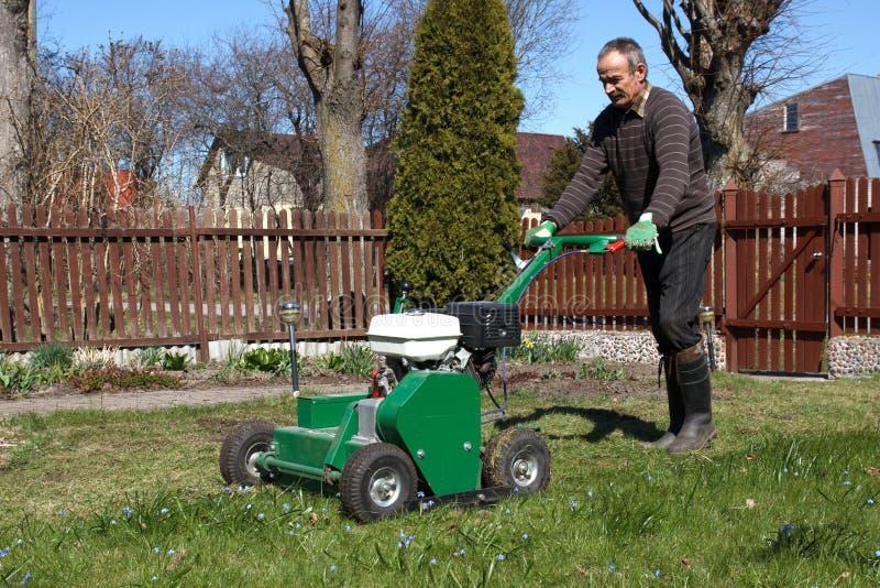 Человек работая с аэратором лужайки стоковое фото