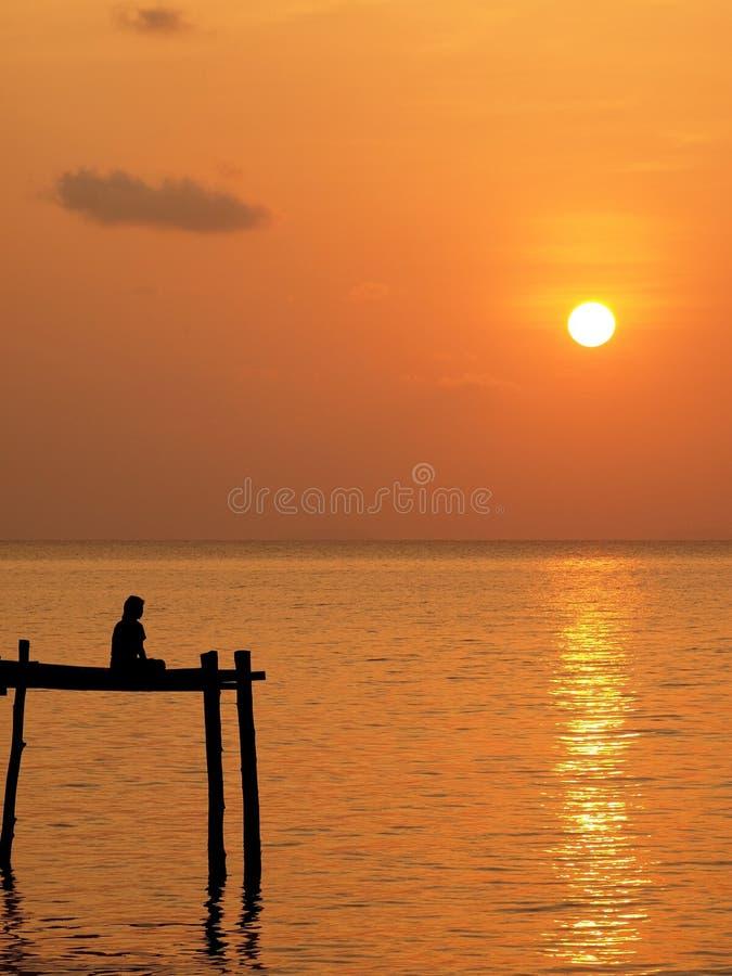 Человек раздумья на деревянной пристани под небом захода солнца стоковое изображение