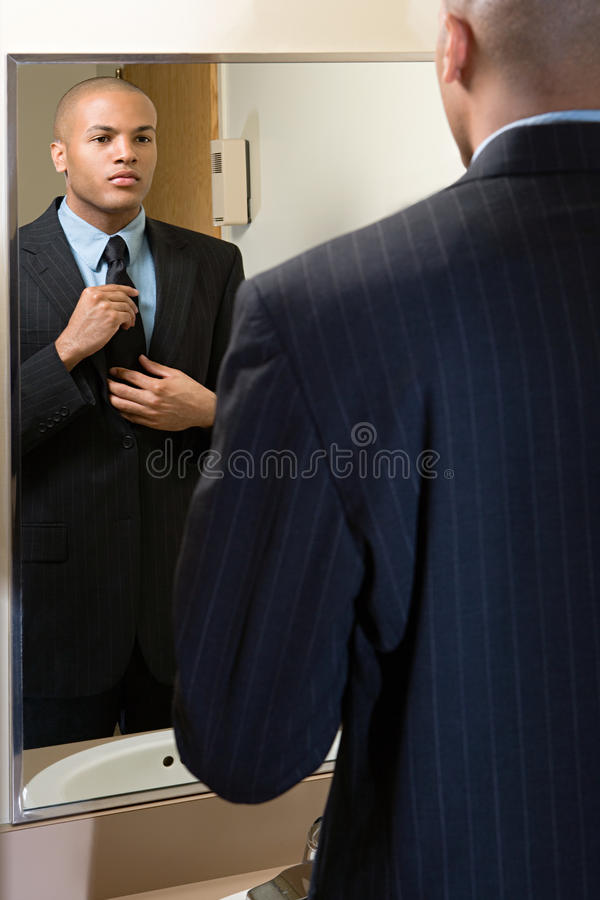 Человек регулируя его связь в зеркале стоковое фото