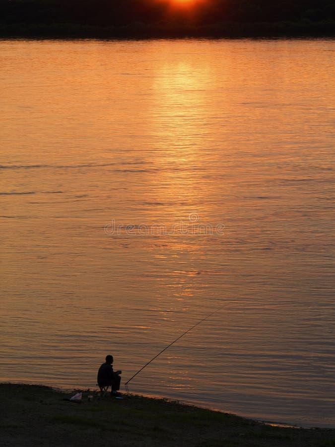 Человек рыбной ловли на заходе солнца стоковая фотография rf