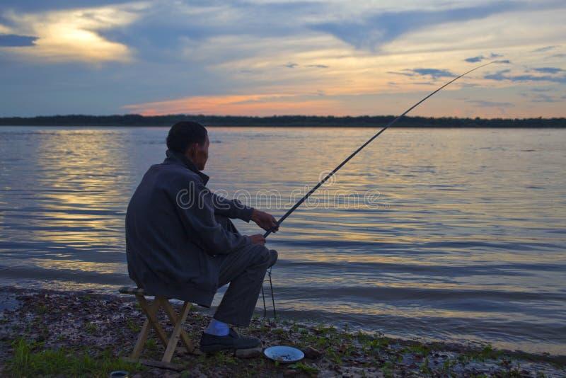 Человек рыболовства на заходе солнца стоковое фото rf
