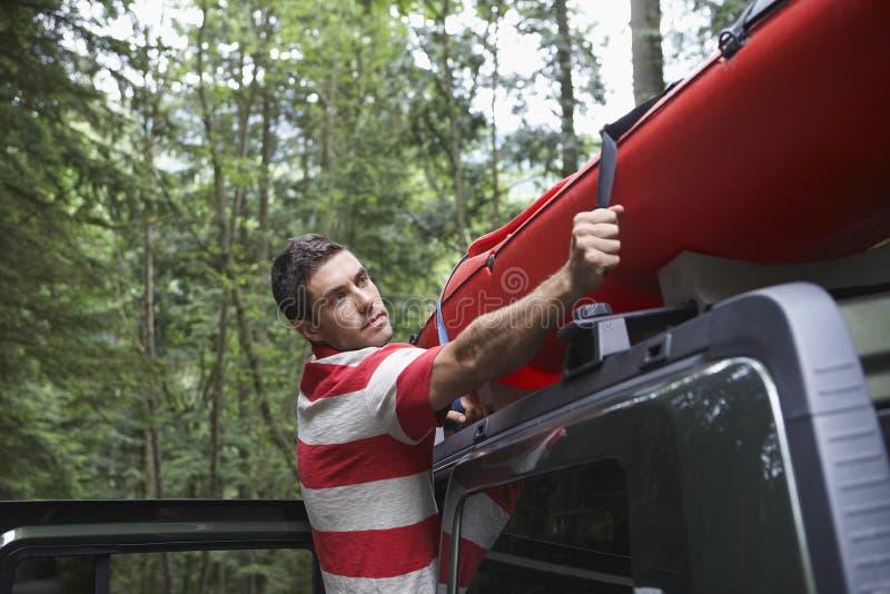 Человек связывая каяк на крыше автомобиля  стоковые изображения rf