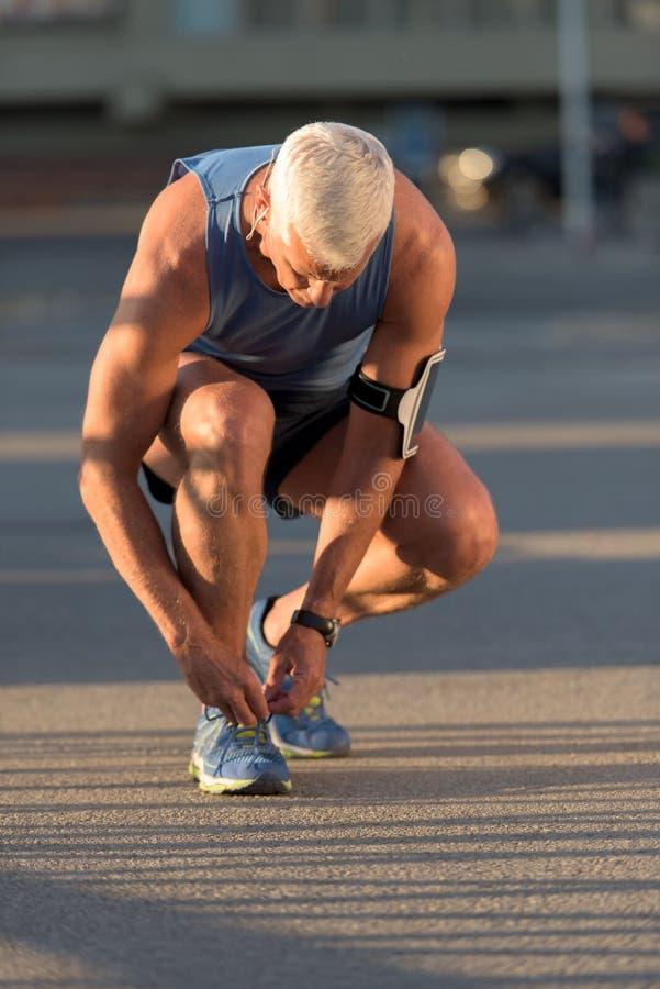 Человек связывая шнурки ботинок хода стоковое изображение
