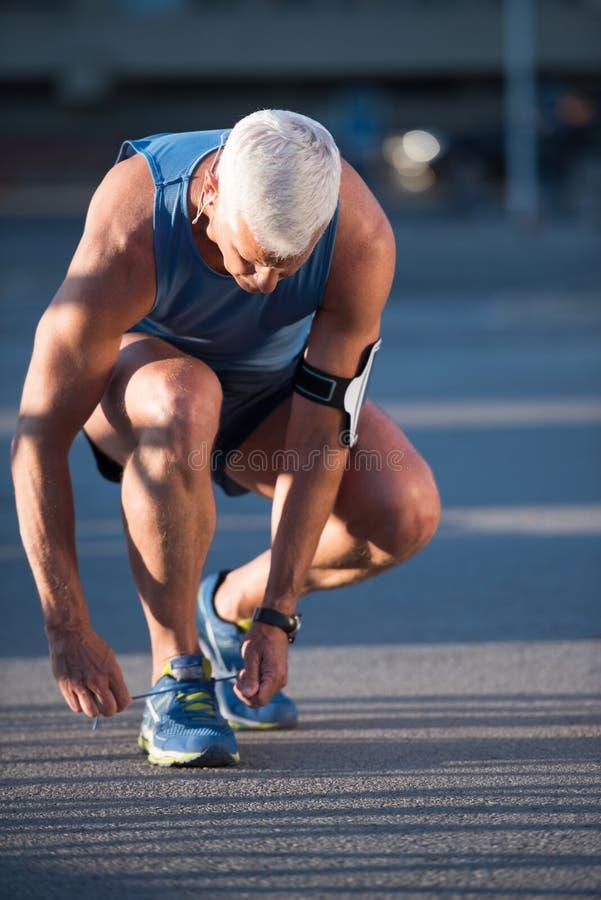 Человек связывая шнурки ботинок хода стоковые изображения rf