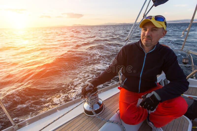Человек сидит на его яхте плавания во время захода солнца стоковая фотография
