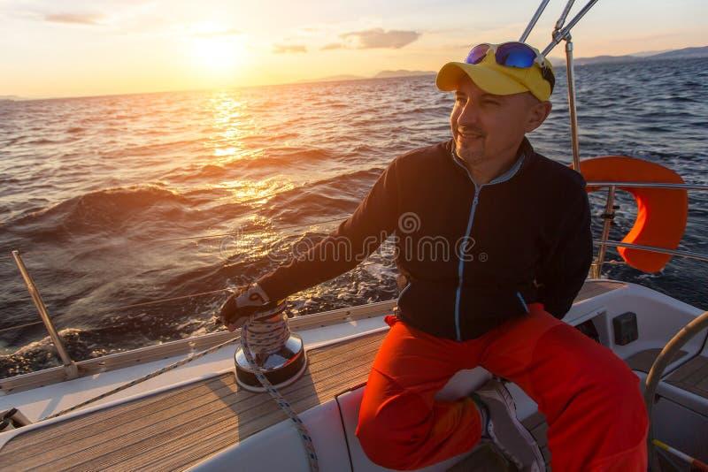 Человек сидит на паруснике во время захода солнца Спорт стоковые изображения rf