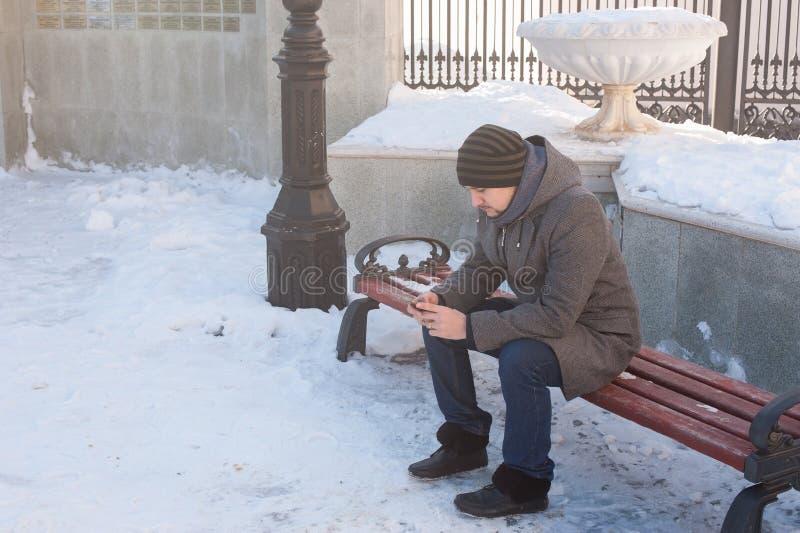Человек сидит на стенде и смотреть телефон стоковые фото
