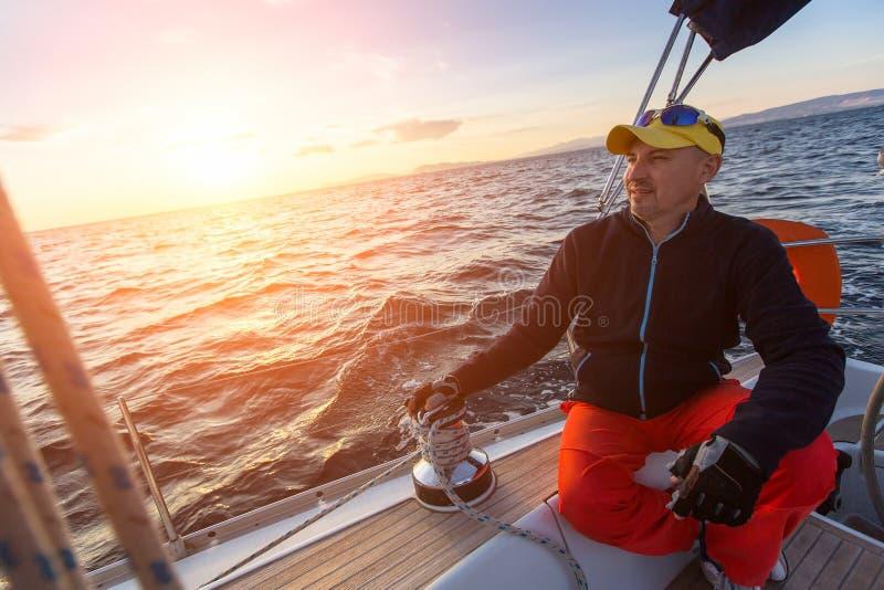 Человек сидит на яхте во время захода солнца Роскошные парусники стоковые изображения