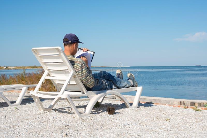 Человек сидит на deckchair морем, начиная проект стоковая фотография