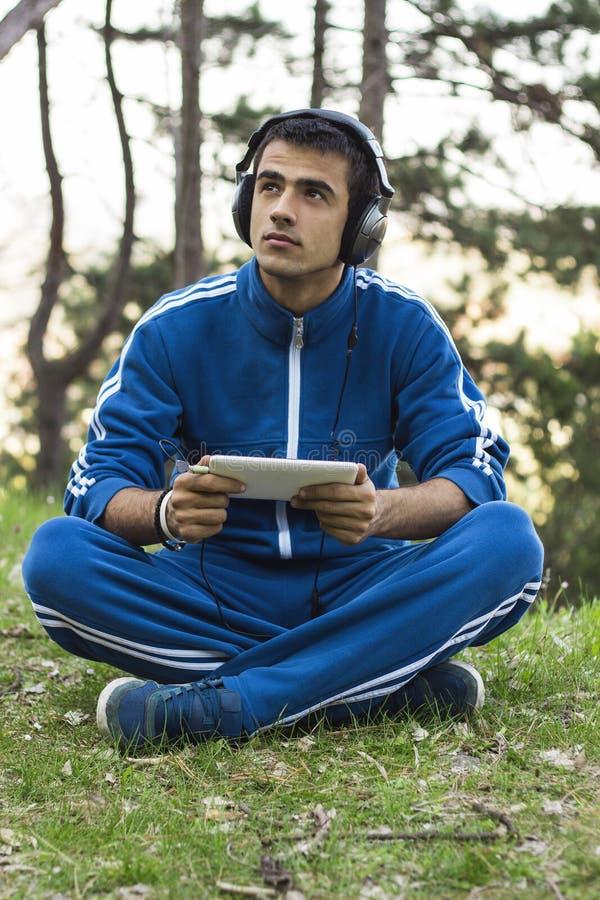 Человек сидит с таблеткой на траве стоковое фото