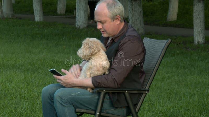 Человек сидит с телефоном и держит собаку акции видеоматериалы